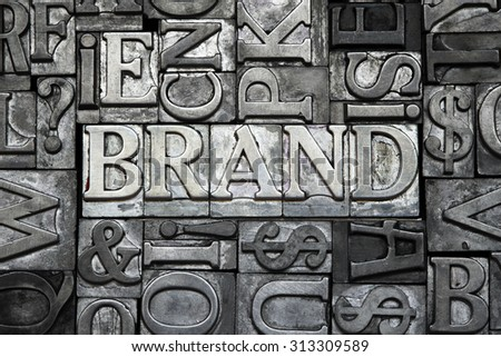 brand concept made from metallic letterpress type with letter blocks background - stock photo