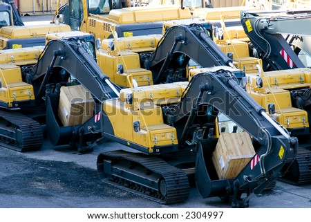 brand new excavators on the shipping dock - stock photo