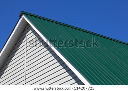 Brand new green rooftop against blue sky - stock photo