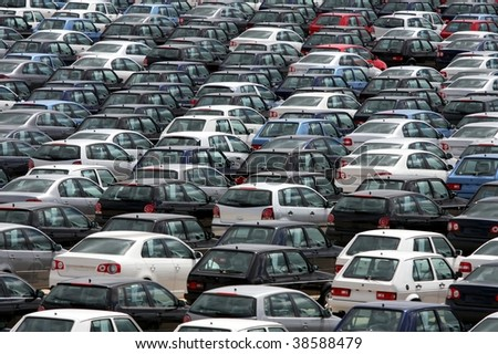 Brand new motor vehicles in a parking lot waiting for export - stock photo