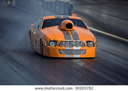 Brand new orange dragster in fast motion down the strip - stock photo
