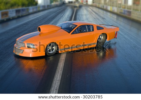 Brand new orange dragster placed on the race course - stock photo