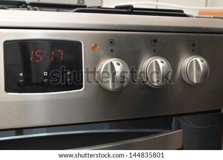 Brand new oven with digital clock and knobs - stock photo