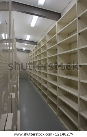 Brand new records storage room, beige metal shelves with lots of space. - stock photo