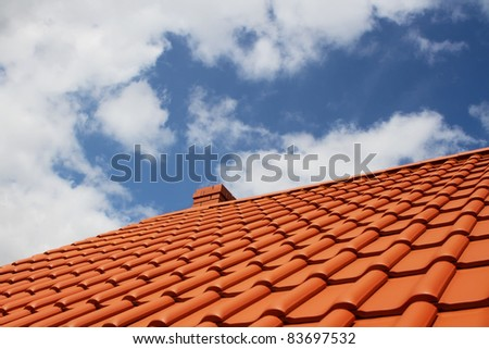 Brand new red rooftop against blue sky - stock photo