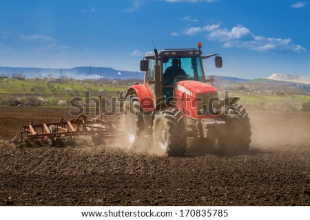 Brand new red tractor on the field working - stock photo