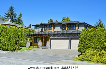 Brand new residential house with landscaped front yard in suburban of Vancouver. Stylish suburban house with double garage and concrete driveway.  - stock photo