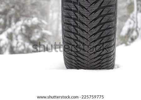 Brand new winter tire on a snow - stock photo