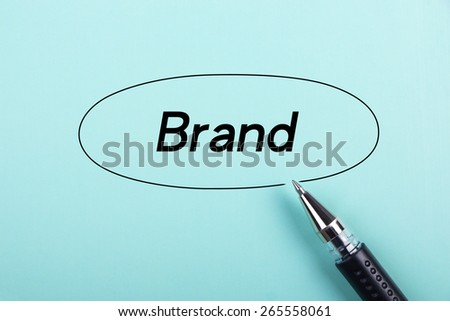 Brand text is on blue paper with black ball-point pen aside. - stock photo