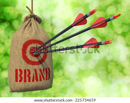 Brand - Three Arrows Hit in Red Target on a Hanging Sack on Green Bokeh Background. - stock photo