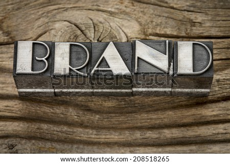 brand word in letterpress metal type printing blocks against weathered grained wood - stock photo