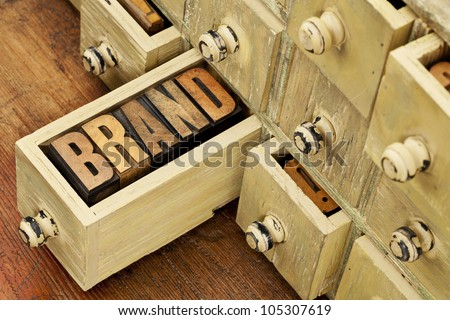 brand word in vintage letterpress wood type in a drawer of antique apothecary cabinet - stock photo