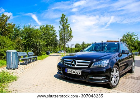 BRANDENBURG, GERMANY - JULY 20, 2014: Motor car Mercedes-Benz W204 C180 at the parking near the interurban freeway. - stock photo