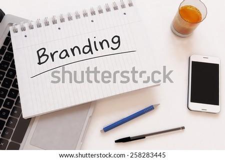 Branding - handwritten text in a notebook on a desk - 3d render illustration. - stock photo
