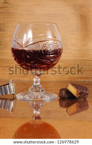 brandy and sweets over wood background