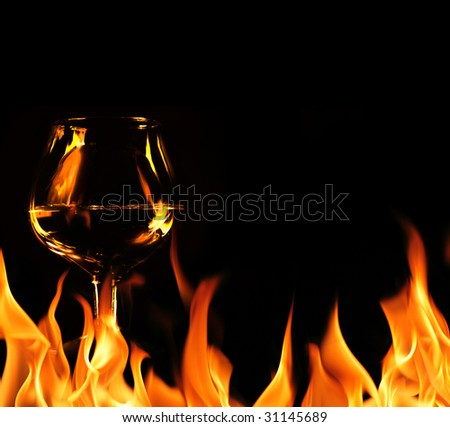 Brandy glass in fire flames - stock photo