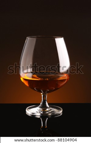 Brandy Glass on black reflective surface and light to dark warm background. Vertical Format. - stock photo
