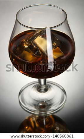 Brandy glass with ice on grey background