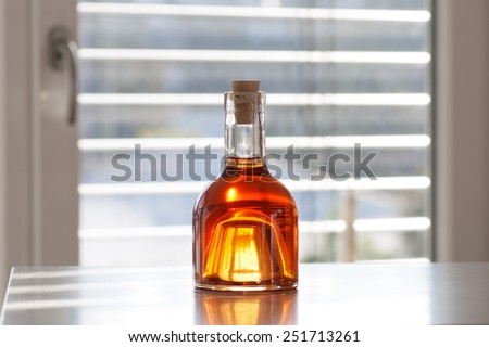 Brandy in a beautiful bottle in front of modern background - stock photo