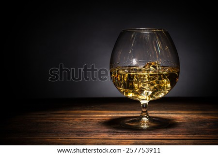 Brandy in glass with ice cube - stock photo