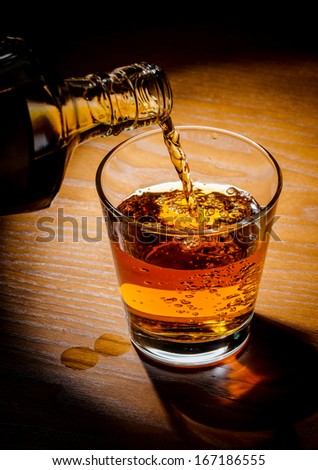 brandy or whiskey pouring into glass on a wooden table