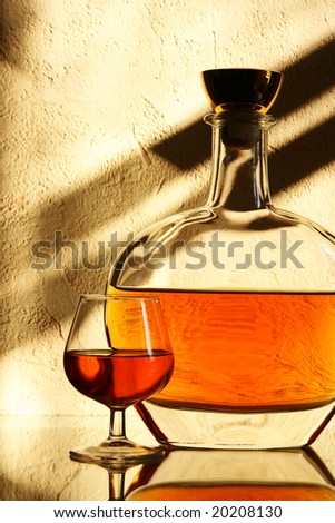 Brandy sniffer glass and bottle close up - stock photo