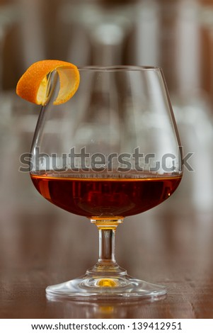 brandy snifter filled with an orange liquor served on a busy bar top garnished with an orange twist - stock photo