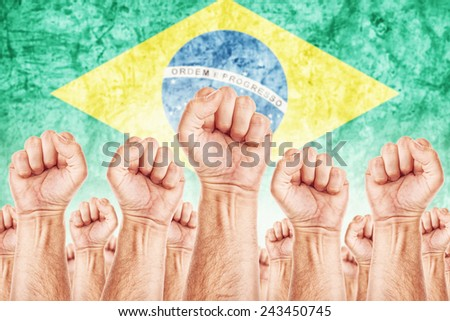Brasil Labor movement, workers union strike concept with male fists raised in the air fighting for their rights, Brasilian national flag in out of focus background. - stock photo