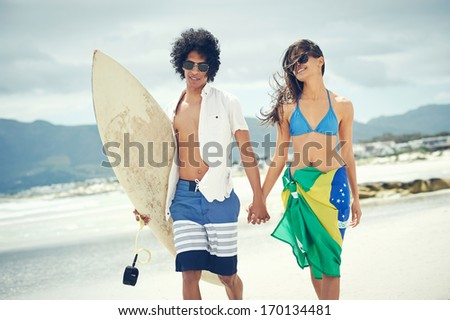 Brasil latino hispanic couple walking holding hands with surfboard and flag as sarong - stock photo