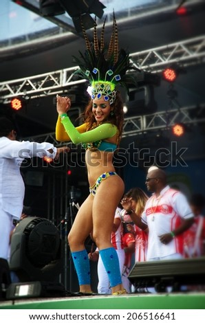 BRASILIA, BRAZIL - JUNE 16: Samba dancer on a stage sensually moving at a concert wearing the colors of Brazil's national flag with the band behind her, on June 16, 2014. - stock photo