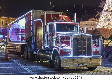 BRASOV, ROMANIA - DECEMBER 11, 2014: A Red Christmas decorated Coca-Cola truck visits Brasov city in the Council Square at night.