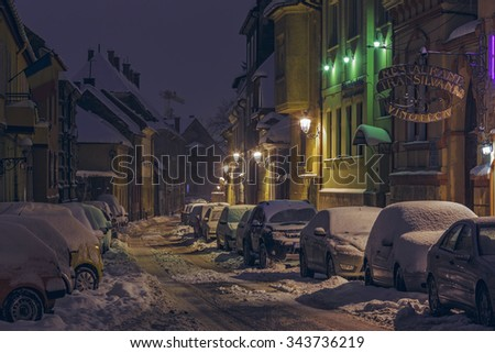 BRASOV, ROMANIA - 29 DECEMBER, 2014: Tranquil winter night scene with snowbound parked cars on a snowy backstreet in the historic center of Brasov, the 7th largest city and most visited in Romania. - stock photo