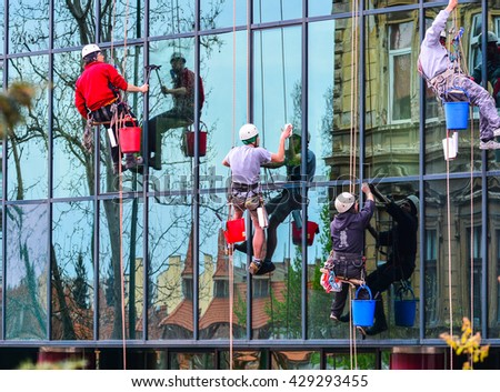 Brasov, Romania - May 31, 2016: Working team of cleaners, cleaning the windows of a building in a town