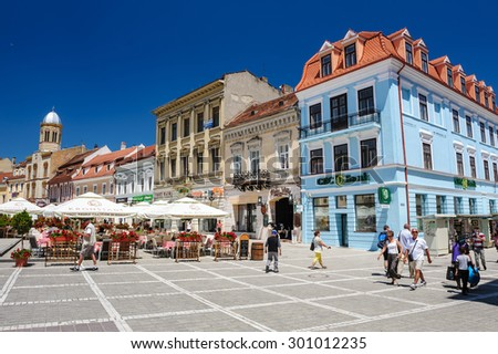 Brasov, Transylvania, Romania, 6th July 2015: Council Square is historical center of city, people walkinng and sitting at outdoor terraces and restaurants. - stock photo