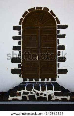 brass brown knocker in a brown closed wood  door and white wall lanzarote abstract  spain canarias  - stock photo
