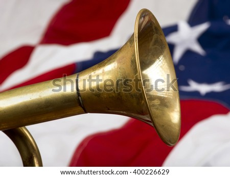 Brass bugle on a American flag . - stock photo