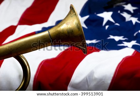 Brass bugle on a American flag with room for your type. - stock photo
