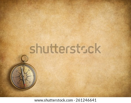 Brass compass on blank vintage paper background - stock photo