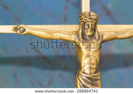 Brass  Cross with crucified Jesus Christ on blue retro background close up