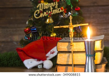Brass Cross with crucified Jesus Christ over black holy bibles with candle light on fore ground  and a decorated Christmas tree over wooden wall as a background, Christian concept - stock photo