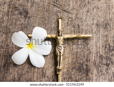 Brass Cross with crucified Jesus Christ with the white flower on wooden background, copy space - stock photo