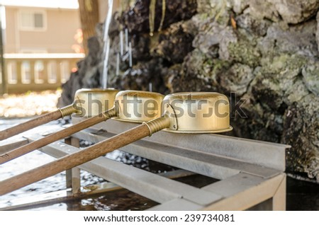 Brass dipper arranged in front of Purification trough in Shinto shrines and Buddhist temple, Japan - stock photo