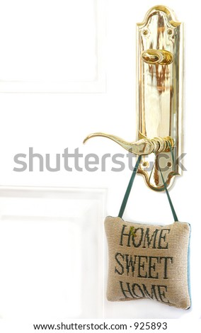 Brass door handle with cross stitched pillow - stock photo