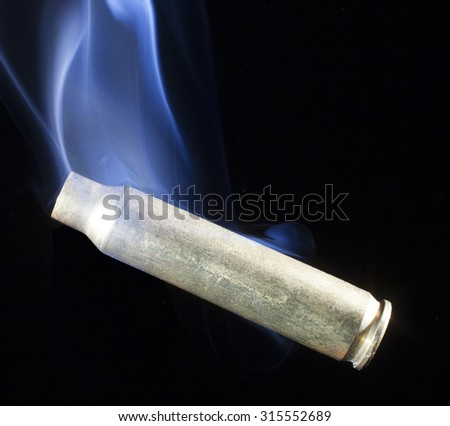 Brass from a cartridge that is smoking after a shot