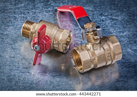 Brass gate lever ball valve on scratched metallic background plumbing concept.