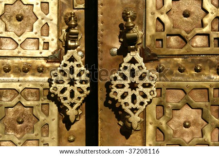 Brass gate with doorknockers. On a house somewhere in medina of Marrakech, Morocco - stock photo