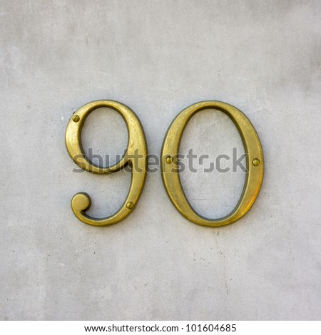 brass house number ninety on a white wall - stock photo