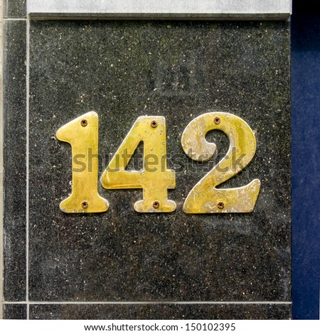 Brass house number one hunded and forty-two on a marble wall panel. - stock photo