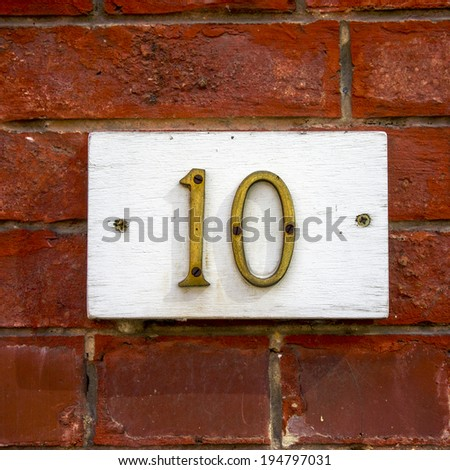 brass house number ten on a wooden plank. - stock photo