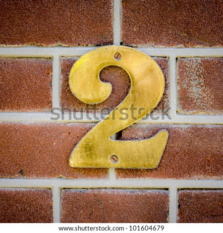 brass house number two on a red brick wall - stock photo
